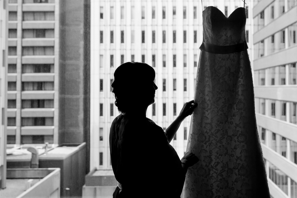 The bride admiring her wedding dress while she gets ready