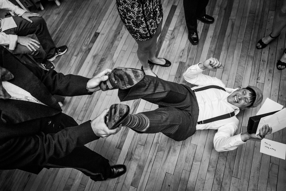 A guest dancing at the wedding reception and being spun around on his back