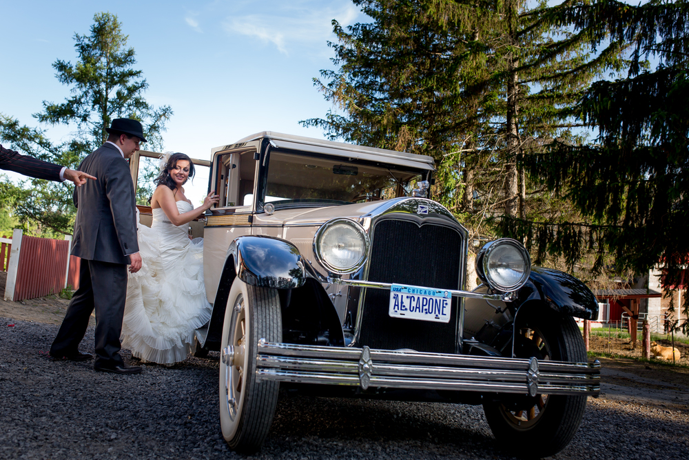 The bride and groom leaving the reception in a vintage car