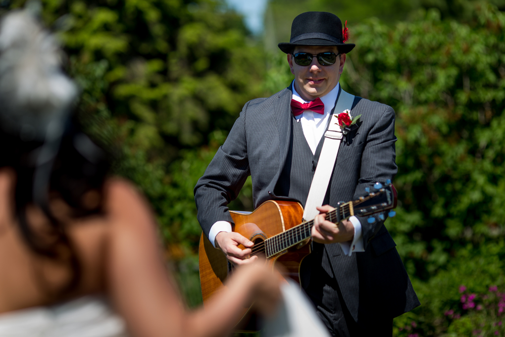 The groom playing the guitar for his bride