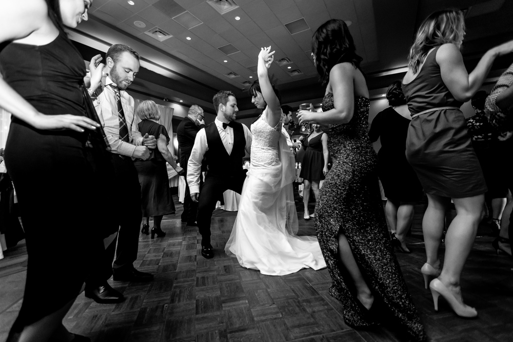 The bride and groom having fun dancing with their friends during their wedding reception
