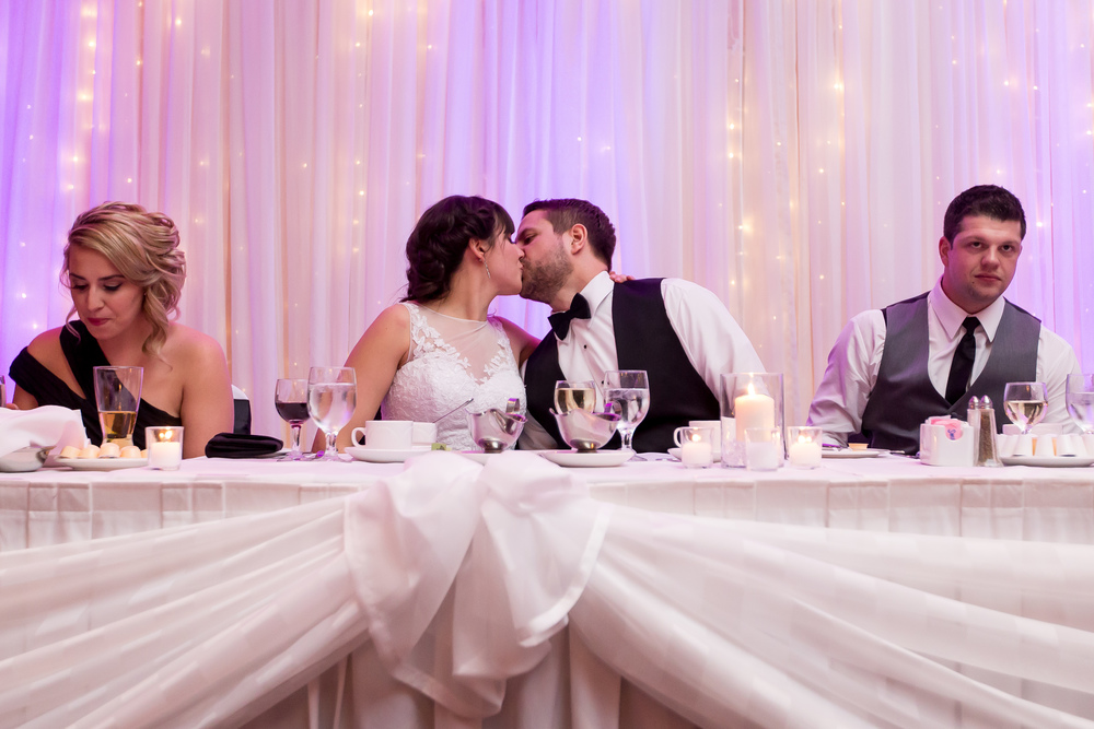 The bride and groom sharing a kiss during their reception speeches