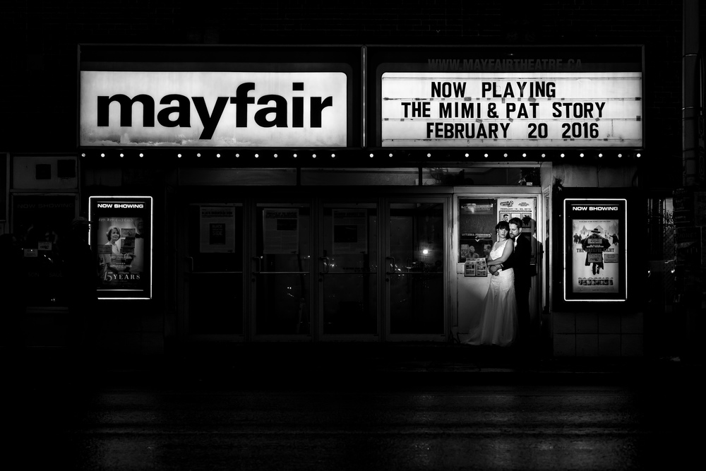 A portrait of the bride and groom outside The Mayfair Theatre