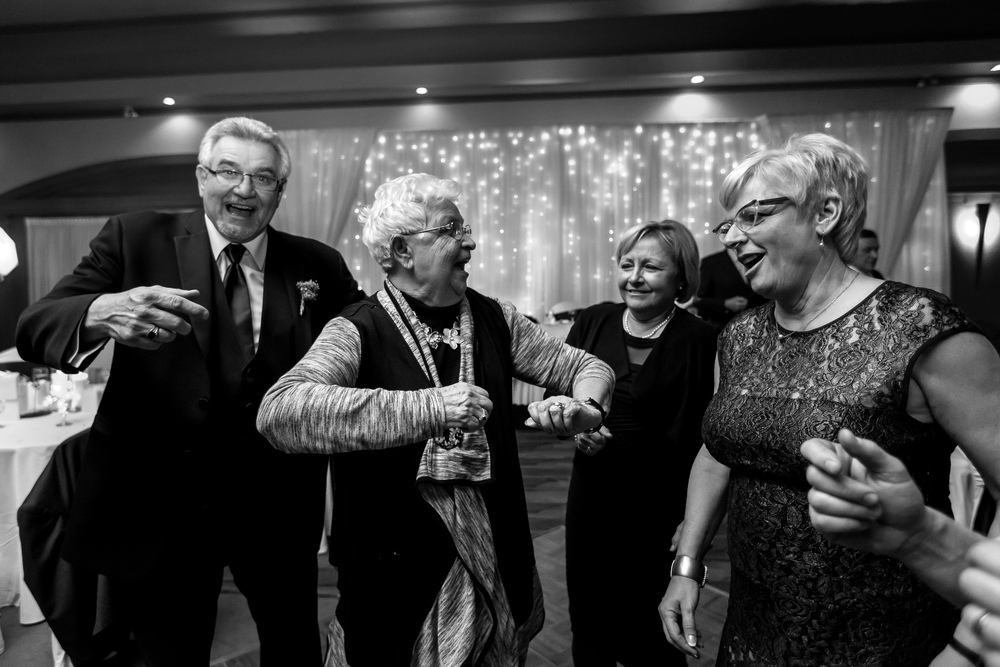 The father and grandmother of the bride dancing with other guests during the wedding reception