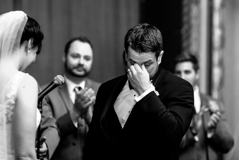 The groom having an emotional moment while the bride reads her vows