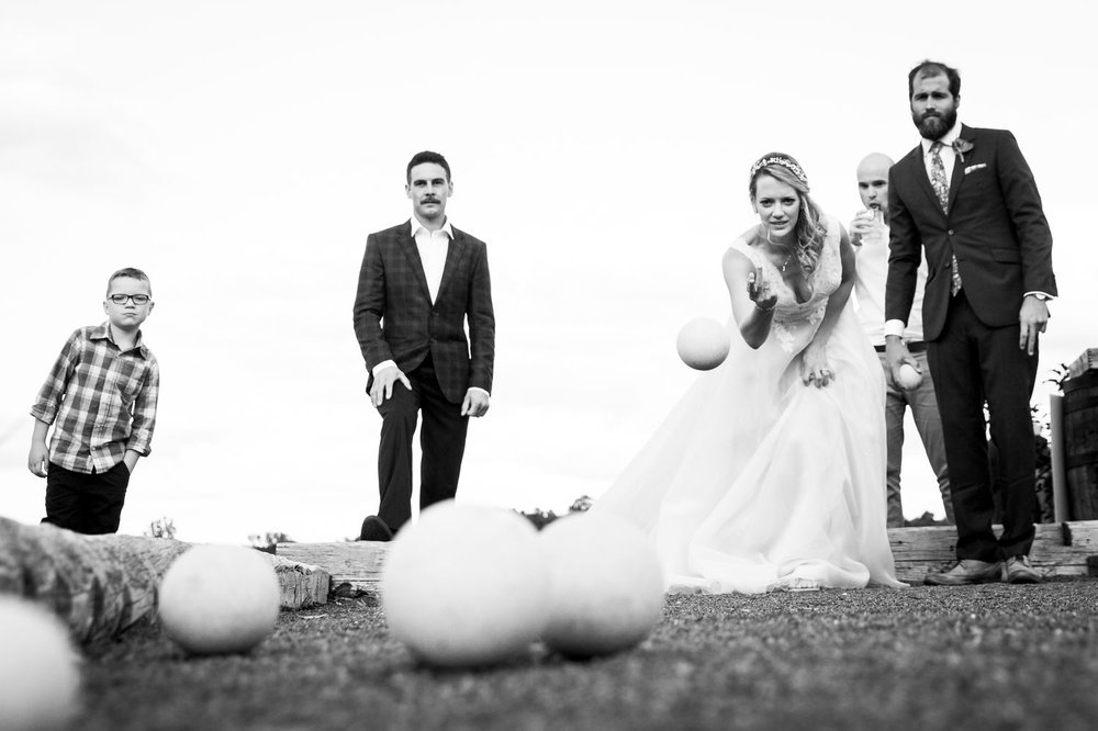 The bride and groom playing bocce ball before their wedding reception at Evermore