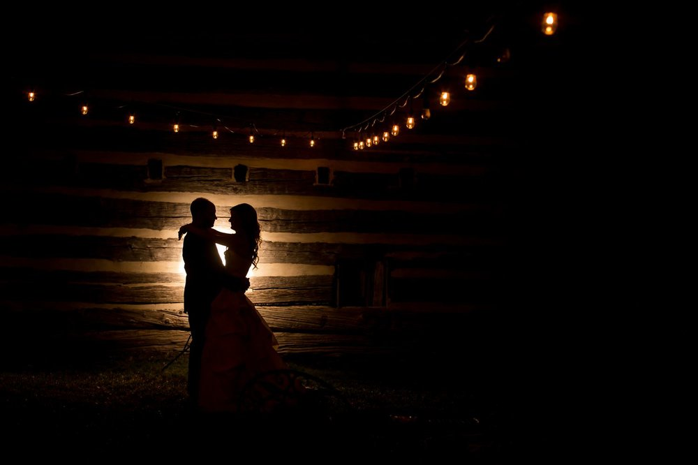 A silhouette portrait of the bride and groom outside the Stonefields barn