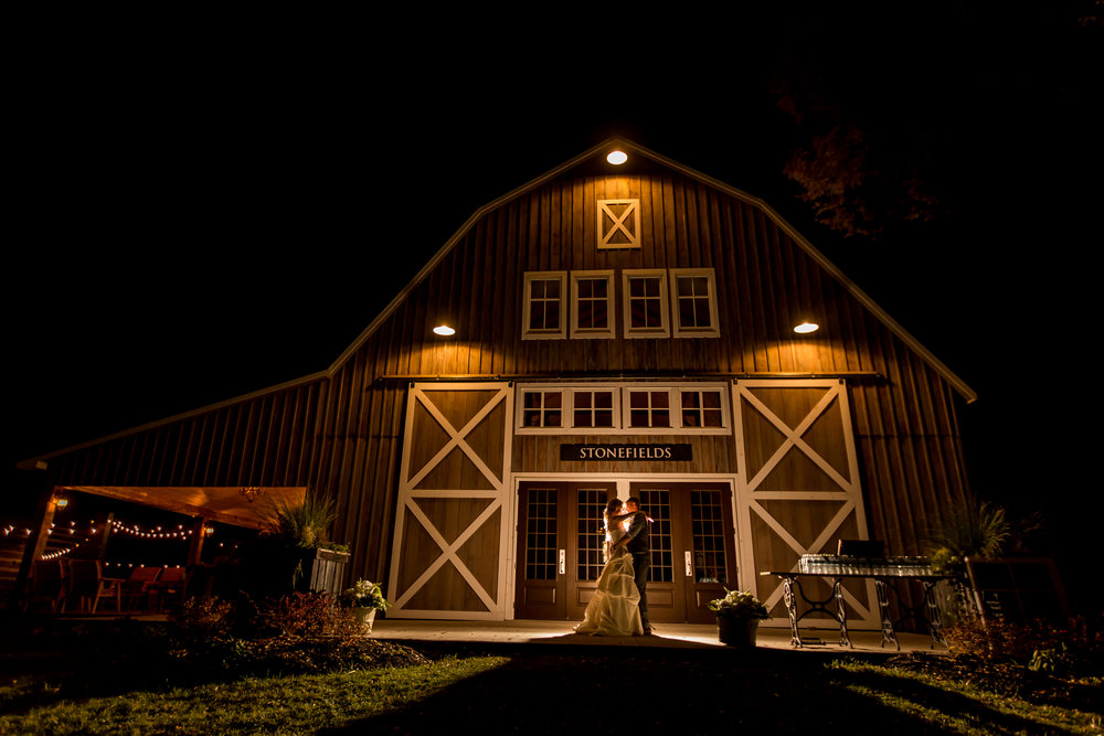 A nighttime portrait of the bride and groom outside the new Stonefields barn