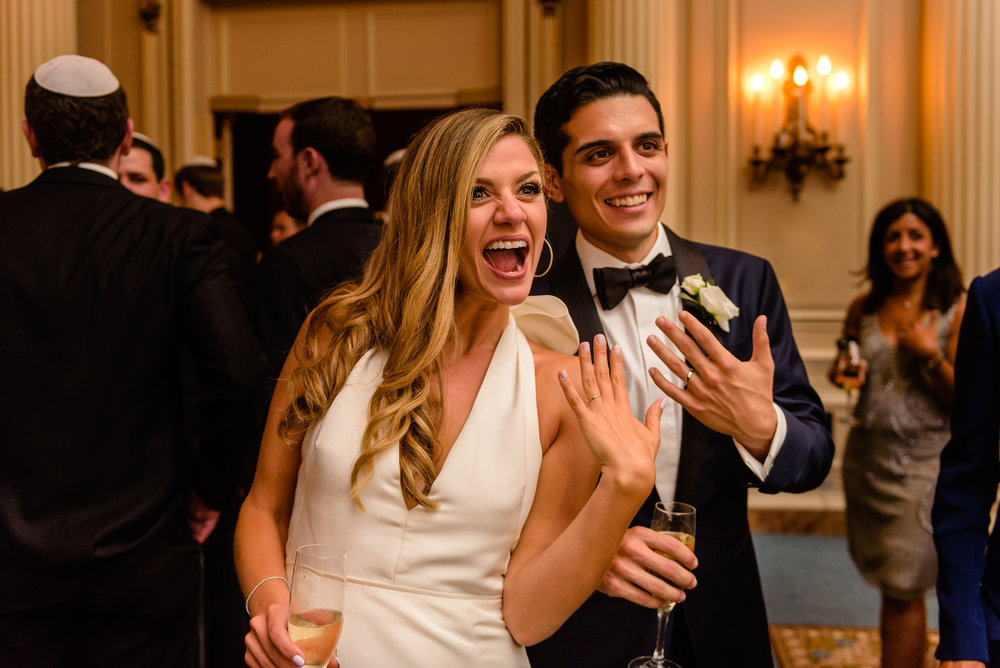bride-and-groom-show-off-their-new-wedding-rings-during-a-wedding-reception-at-a-fairmont-chateau-laurier-in-ottawa.jpg
