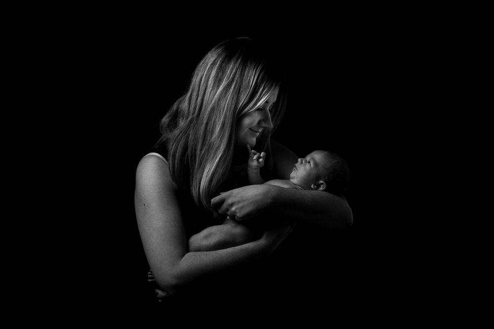 black and white photograph of a mom with her newborn baby