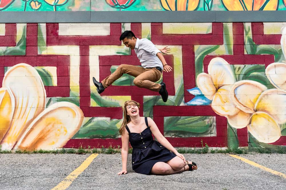 a funny engagement photo with the guy jumping over the girl
