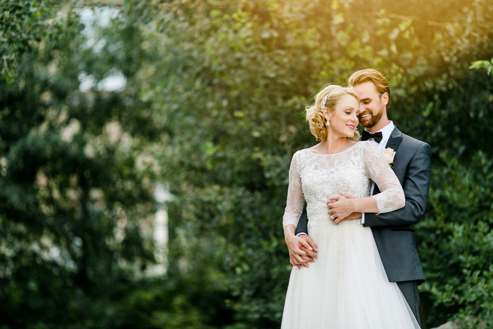 sunny photo of a bride and groom in front of some trees at the Museum of Nature in Ottawa