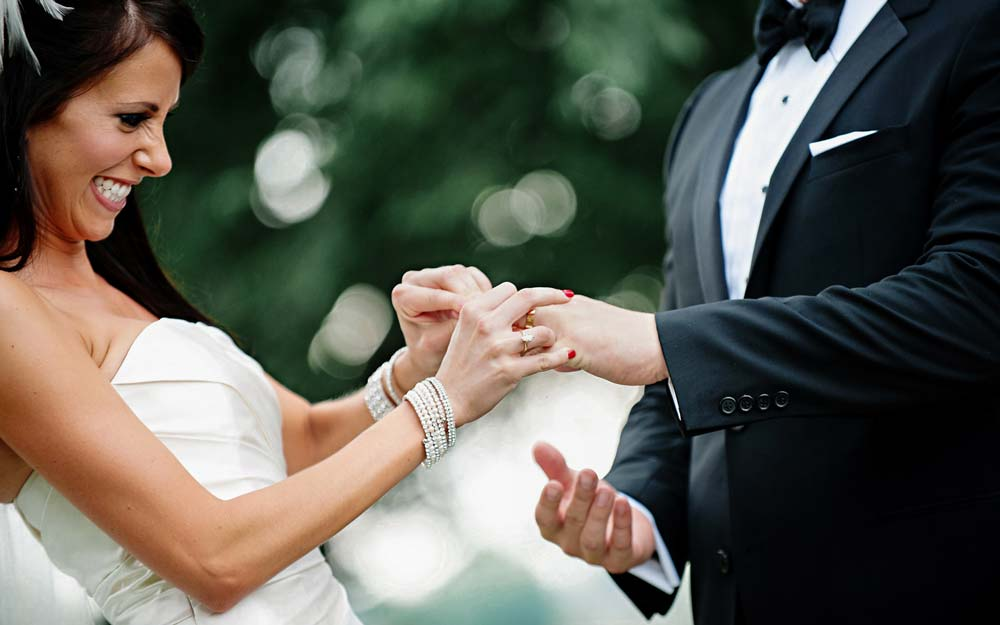 a bride trying to put a ring on her grooms finger