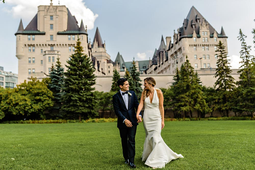 Bride and groom walking in front of the chateau laurier in ottawa