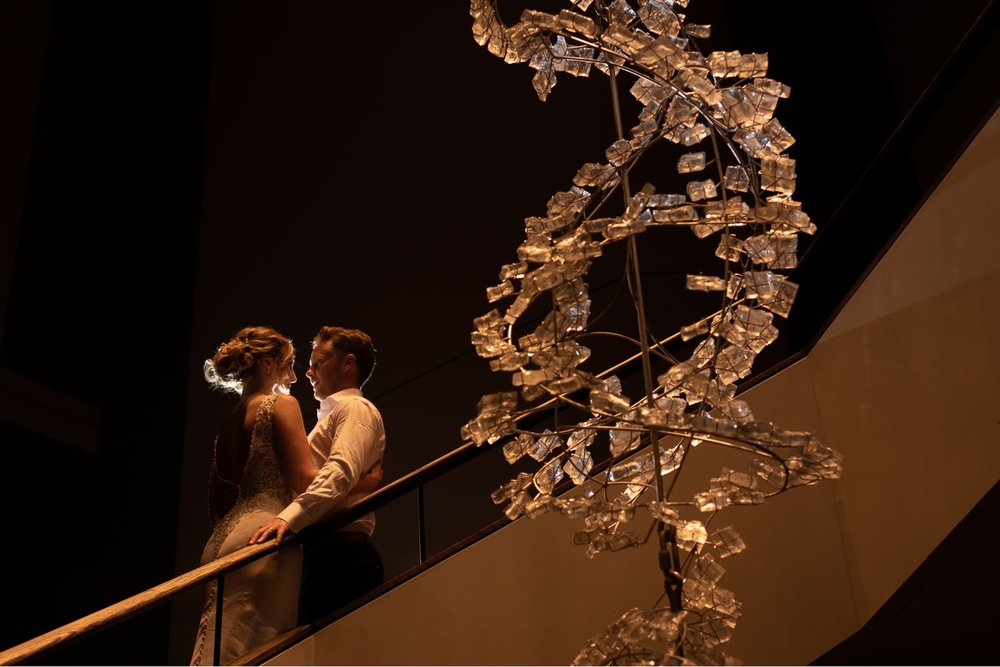 A portrait of the bride and groom taken at night inside The National Arts Centre in downtown Ottawa