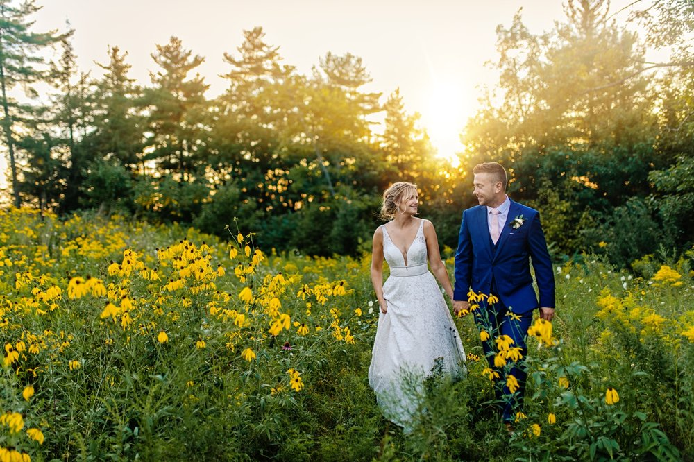 bride and groom have a walk through flower field at sunset at le belvedere in wakefield quebec