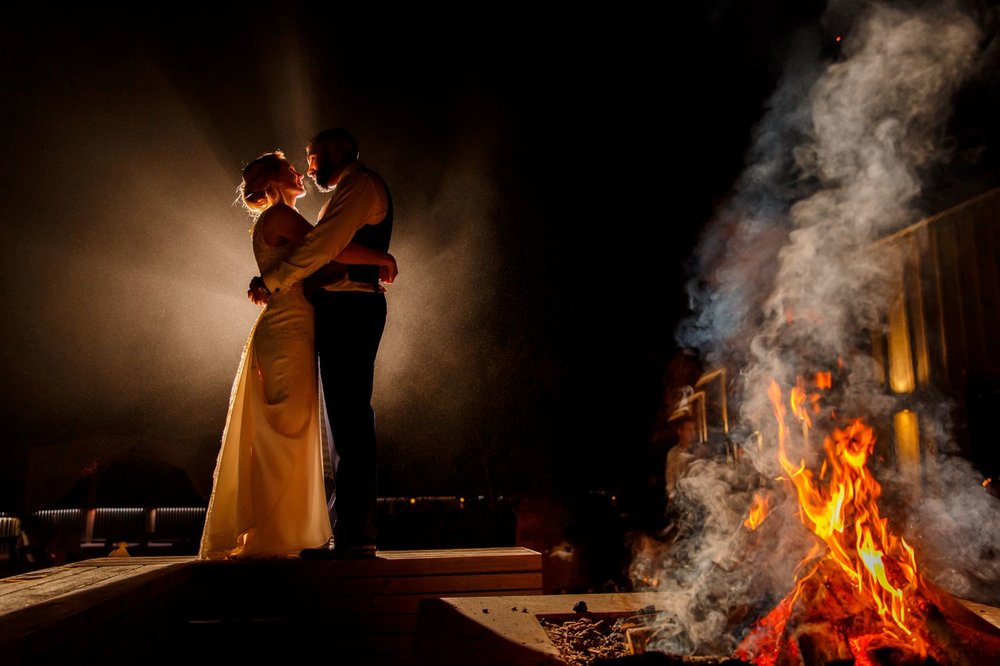 A night portrait of the bride and groom by the fire outside at Le Belvedere