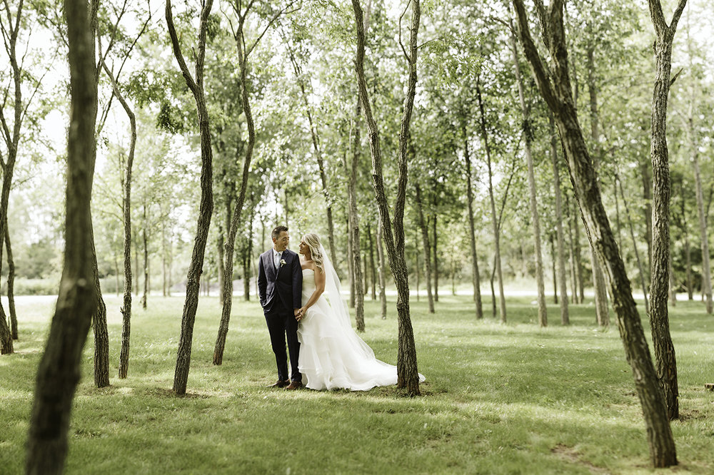 bride and groom portrait in the trees before a wedding ceremony at stonefields in carelton place ontario