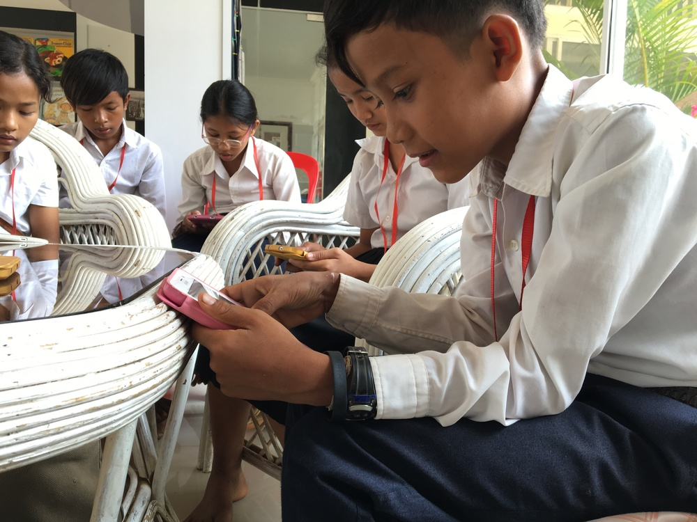 Students from a school in Phnom-Penh, Cambodia reading books from Library For All's digital library on their tablets. This program occurred in partnership with The Asia Foundation.