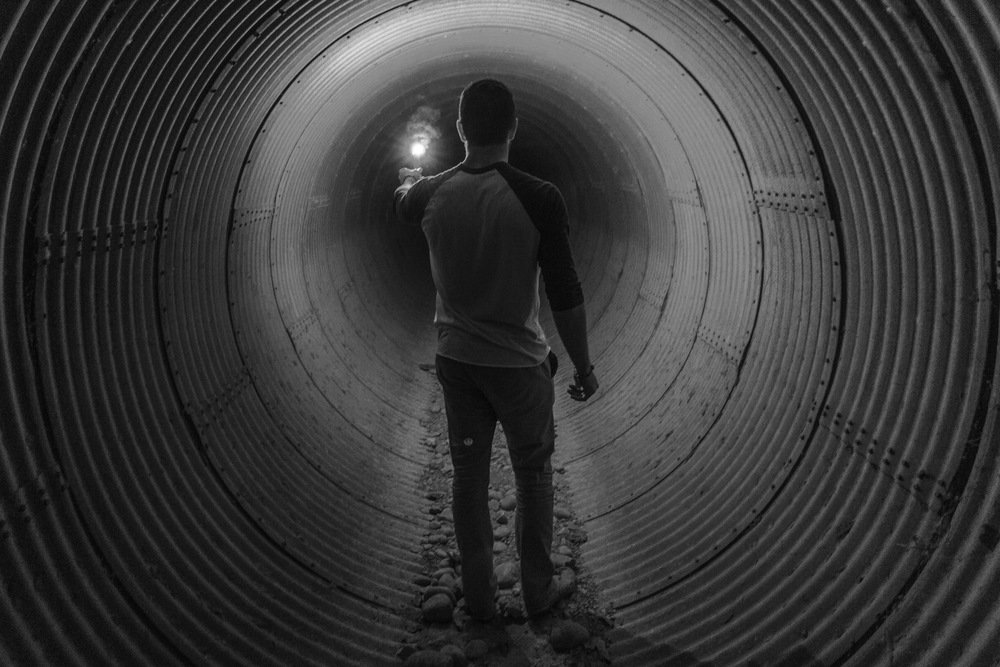 Man walking through tunnel with match