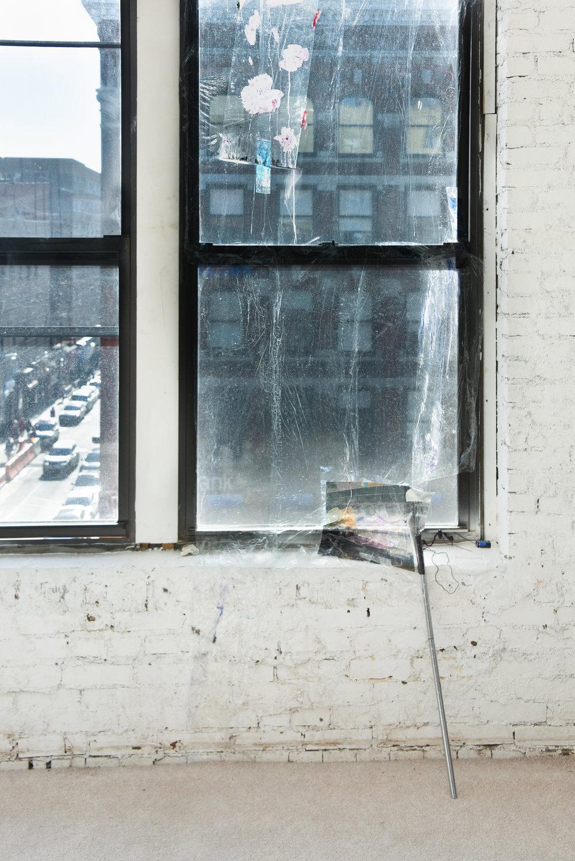 Water Spill is Waterfall (window,)Irina Jasnowski Pascual Saran wrap, acrylic paint, mylar, image transferred on tape, window cleaner spray, LED light, 9v battery, earbud speaker, metal shelf leg