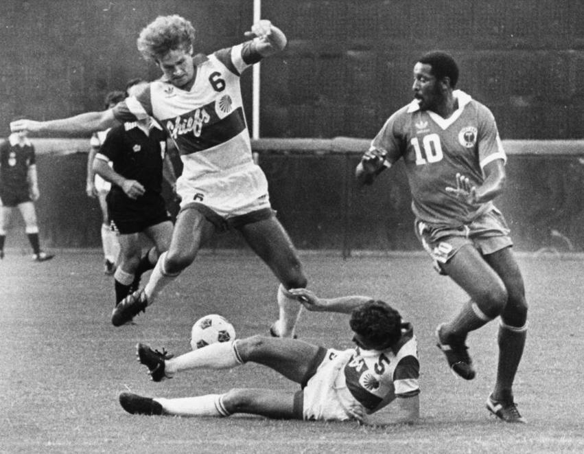 Atlanta Chiefs Stuart Lilley 6 avoids a fallen teammate in a photo from the 1980s.jpg