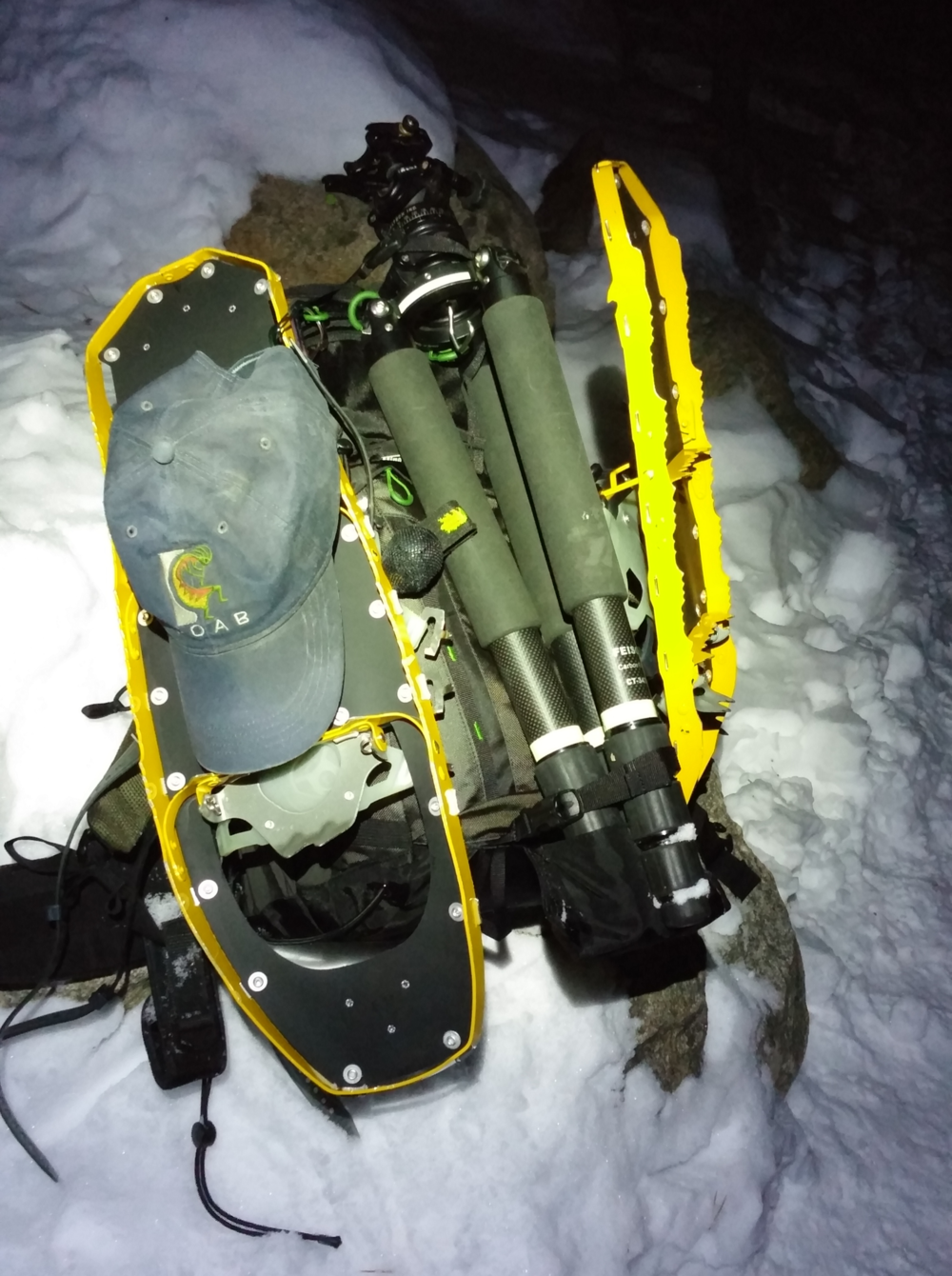 Mike has a tripod hanging on the back middle of the Backlight 26L and snowshoes on the sides.