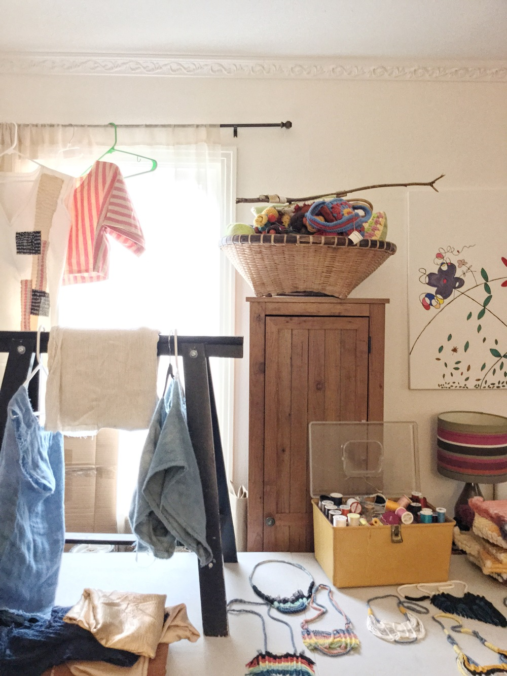 The home studio: Draped in sunlight, bits and baubles decorate the workspace. Her gorgeous necklaces prepare to ship out.