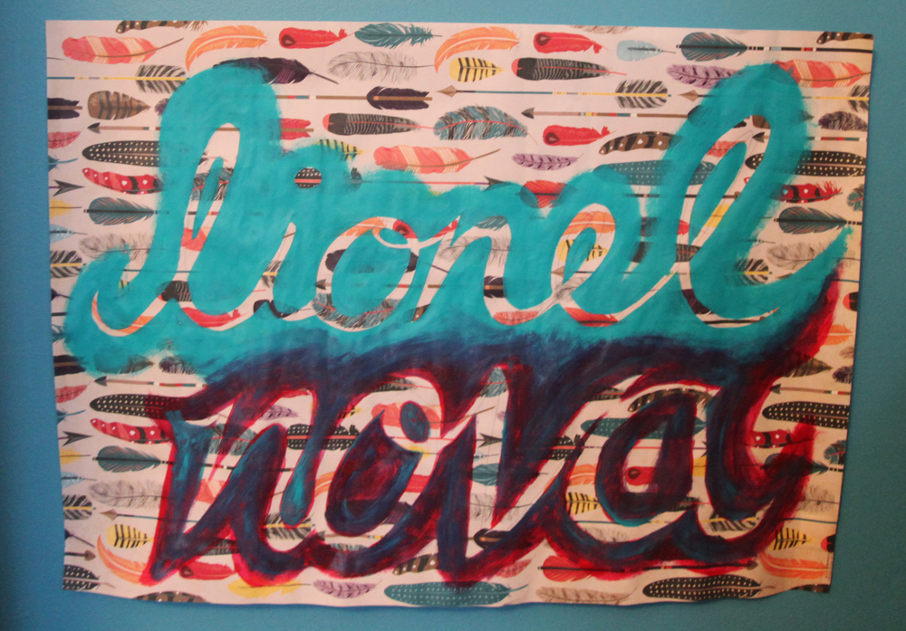 """Benny painted the scripted """"Lionel Nova"""" sign on wrapping paper."""