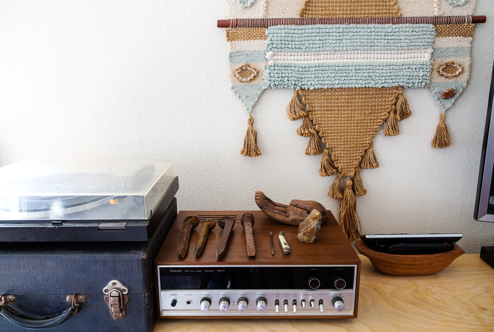 A vintage record table vignette. Flea-found railroad spikes, wooden palm, and an original Don Freedman fiber wall hanging from the '70's.