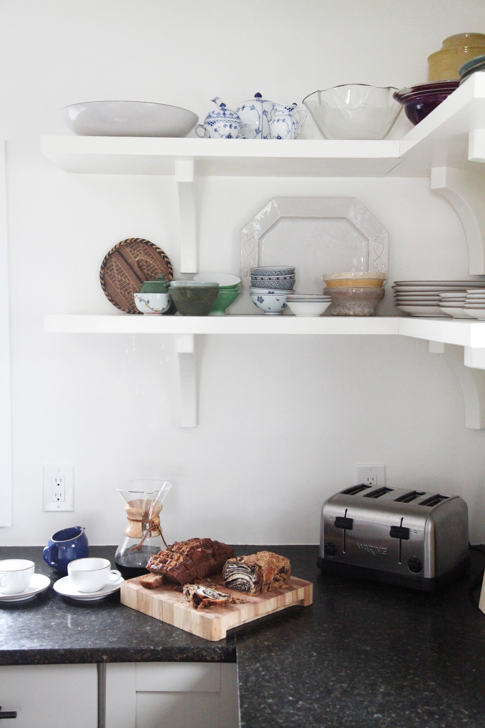Tidy vintage dish stacks on exposed shelving.
