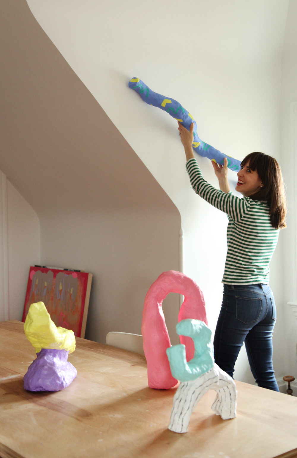 Playing with the wiggly snake, her first sculpture. We're pretty much obsessed with the bubblegum colors and oddly-attractive shapes in her collection.