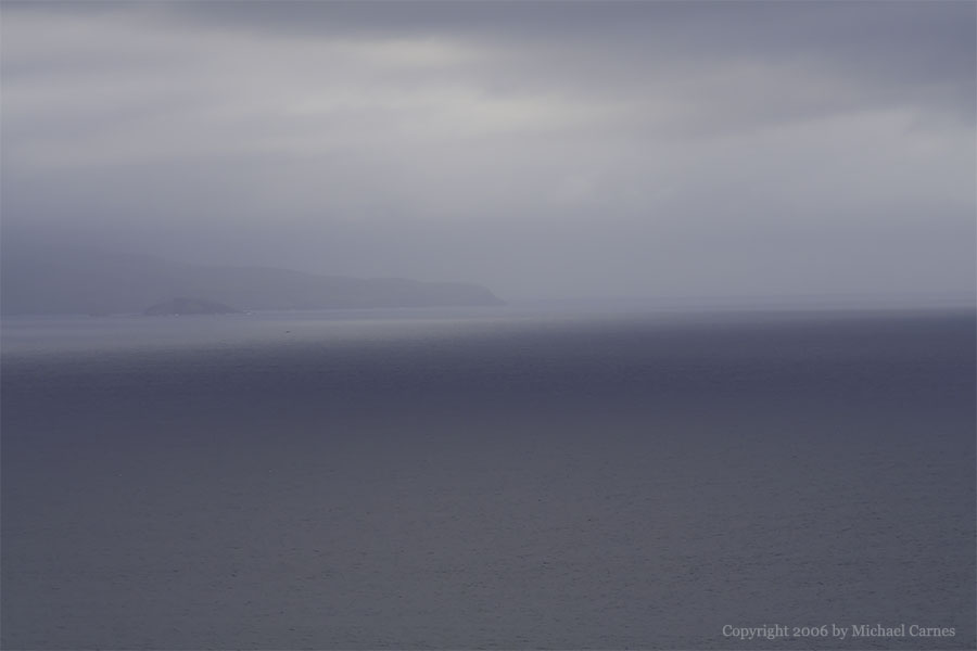 The island of Molokini, viewed through fog on Maui