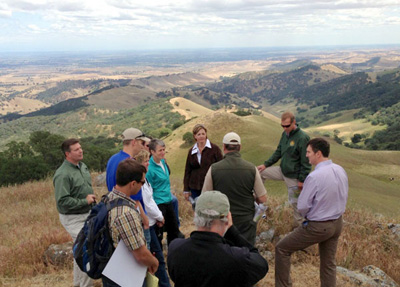 U.S. Secretary of the Interior Sally Jewell (center, in turquoise) visits Kreigor Peak with local staff and dignitaries to discuss conservation successes and take in sweeping views of land conserved through the East Contra Costa County Plan. Photo: May 2014.