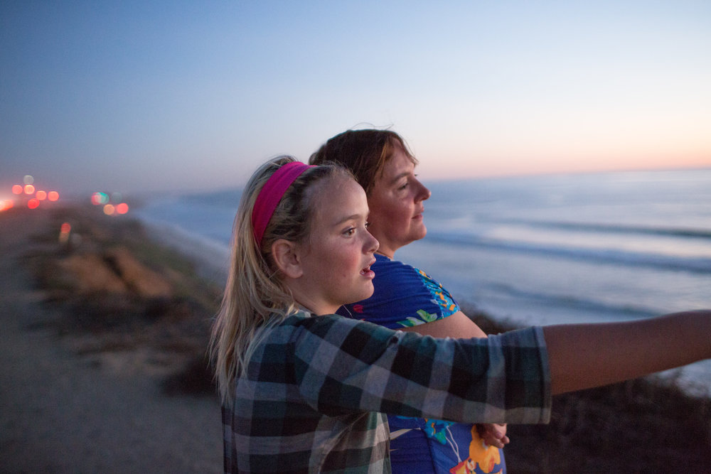Ruby points out dolphins in the ocean to her mother Allie in Carlsbad, CA.