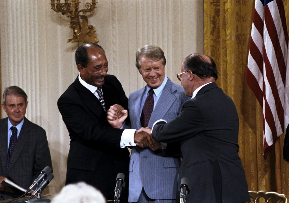 Triple handshake with Carter, Sadat, and Begin in the East Room, September 17, 1978. Depending on their culture, some of the men in this picture may have been comfortable with the nearness than others.   CIA/Wikimedia Commons  (public domain)