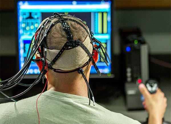 A test subject at the US Airforce's Non-Invasive Brain Stimulation lab uses a controller to navigate a set of computer tasks. Electrodes for targeted brain stimulation are attached to his head. J.M. Eddins, Jr./US Air Force (CC BY 2.0)