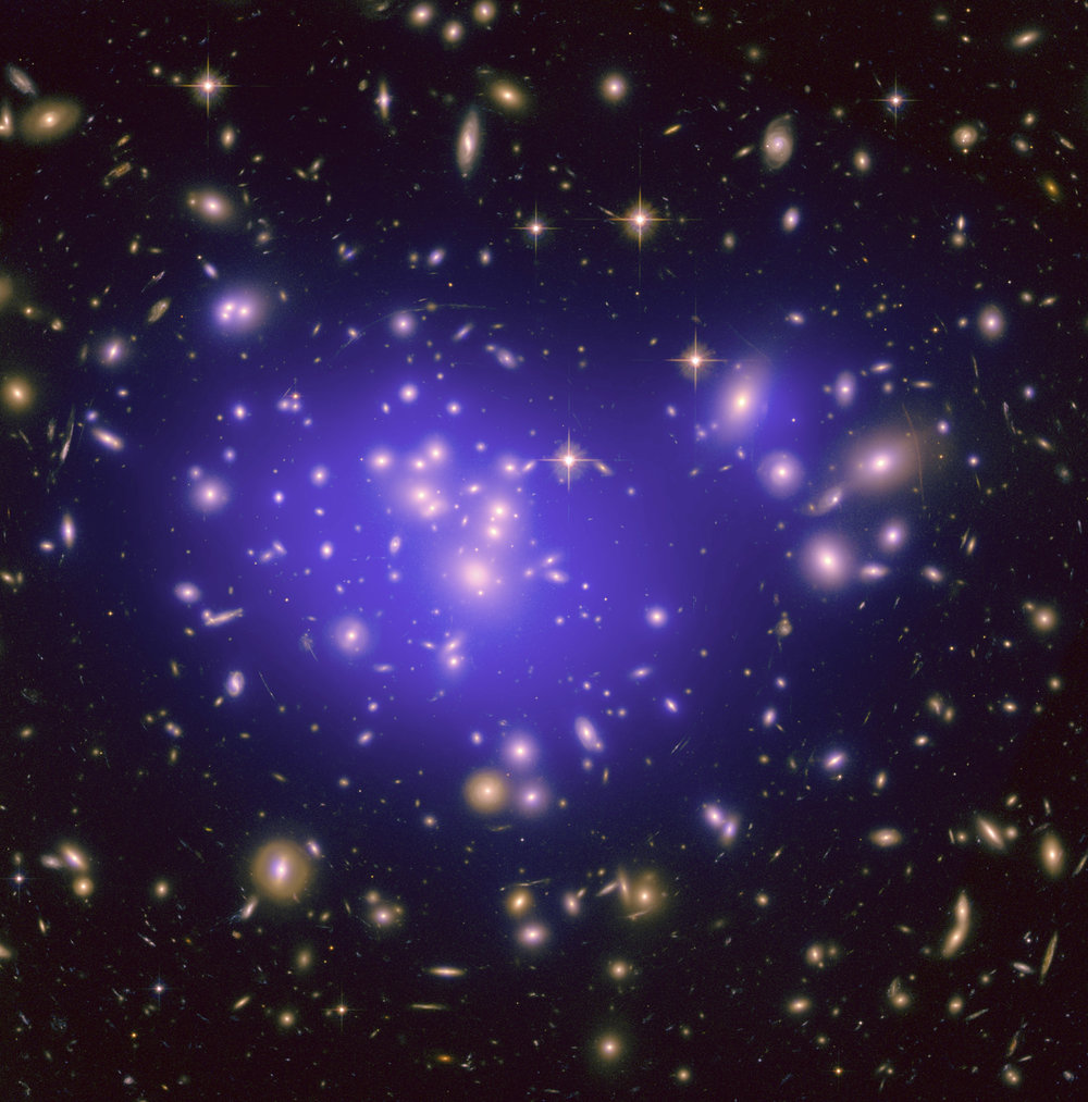 This Hubble image of the galaxy cluster Abell 1689 shows the probable distribution of dark matter overlaid in purple.   NASA, ESA, E. Jullo (JPL/LAM), P. Natarajan (Yale) and J-P. Kneib (LAM)/Flickr  (CC BY 2.0)