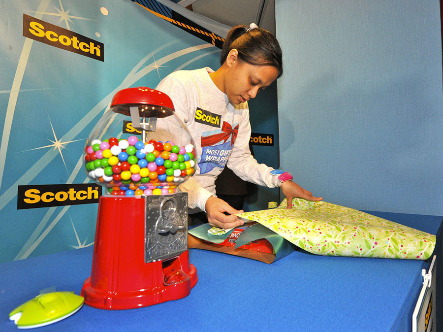 Diana wraps a giant gum ball machine at the 2011 Scotch Brand Most Gifted Wrapper Contest. Photo courtesy of Scotch™ Brand ( http://www.scotchbrand.com/3M/en_US/scotch-brand/ ): photographed by Ray Stubblebine (INSIDER IMAGES)