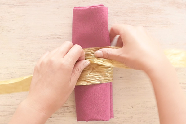 Step 1: Fold the napkin into an appropriate size. Wrap the paper ribbon around the napkin, making sure the short end stays on the right side.