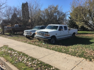 some pickuptrucks in a lot next to a house.