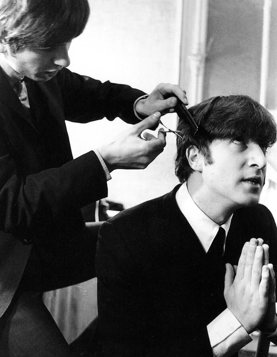 George Harrison cutting John Lennon's hair, circa 1964.