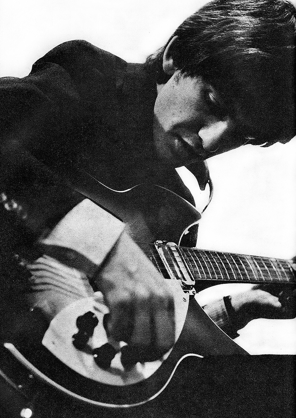 George Harrison tuning his guitar, 1964.