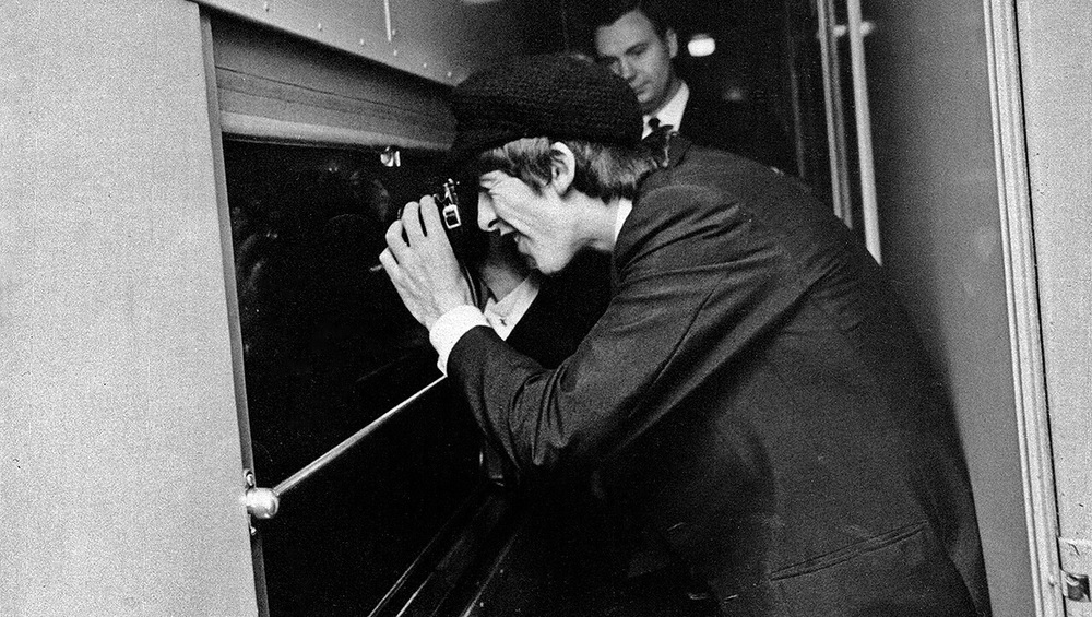 George Harrison taking a picture out a train window, 1964.