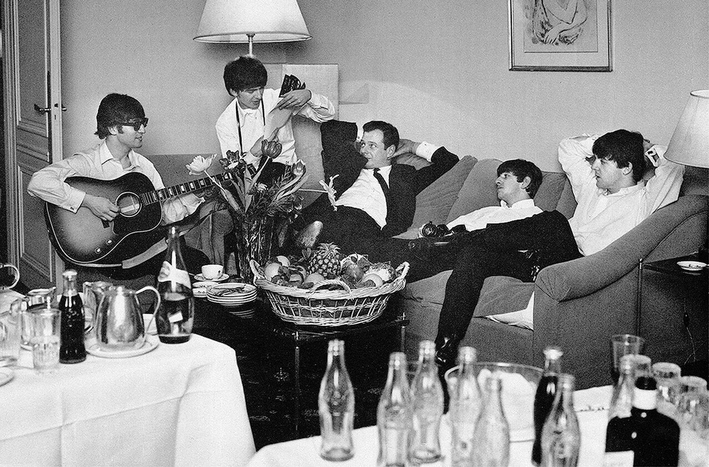 The Beatles jamming in a hotel room with manager Brian Epstein, circa 1964.