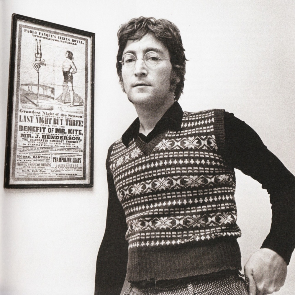John Lennon standing by the poster that inspired Being for the benefit of Mr. Kite! circa 1971.