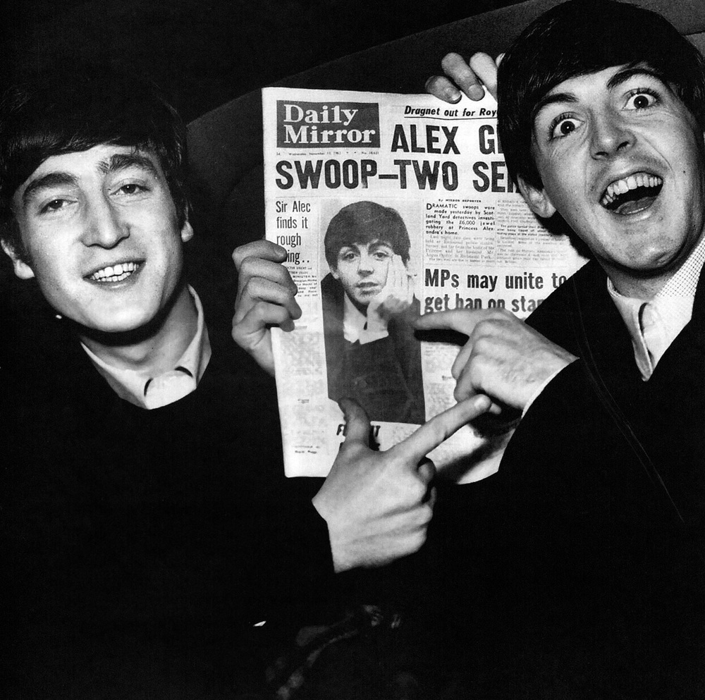 John Lennon and Paul McCartney reading about themselves in a newspaper, 1964.