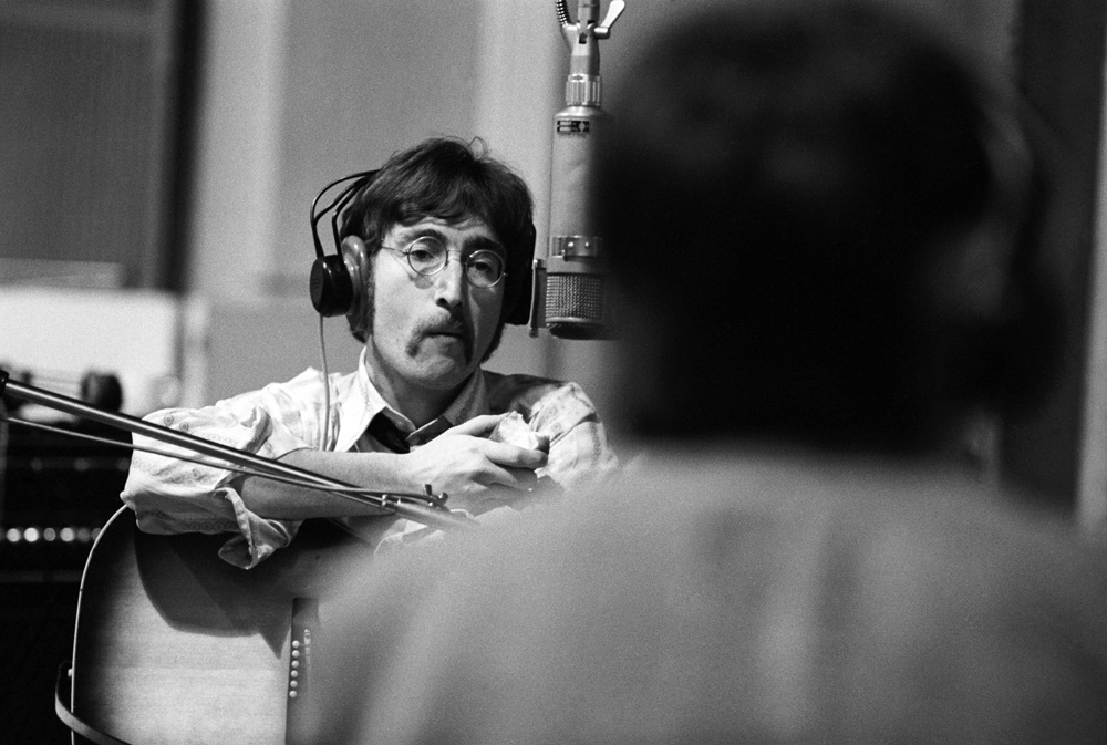 John Lennon eating an apple at a Sgt. Pepper recording session, 1967.