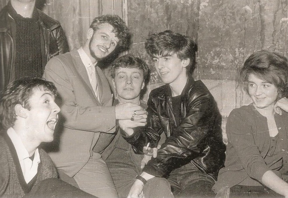 Paul McCartney, Ringo Starr and George Harrison enjoying a drink with friends, circa 1962.