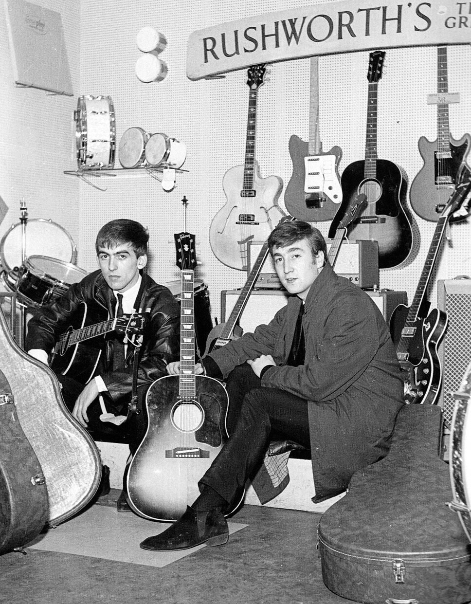 George Harrison and John Lennon in a guitar shop, 1962.